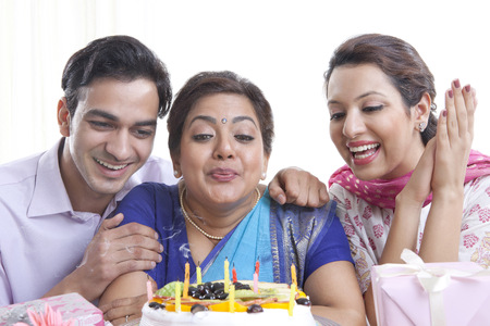 kameez: Woman blowing out candles on a birthday cake Stock Photo