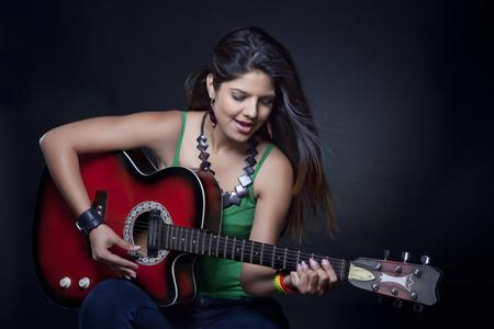 'eyes shut: Young woman playing the guitar