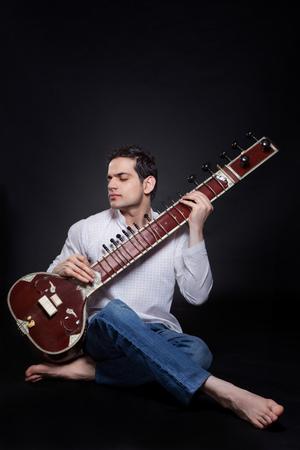 'eyes shut: Young man playing the sitar Stock Photo