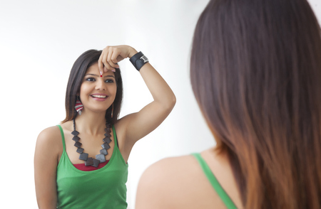 Young woman looking at herself in the mirror Stock Photo