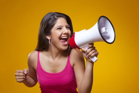 mega phone: Young woman screaming into a megaphone