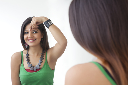 admiring: Young woman looking at herself in the mirror Stock Photo