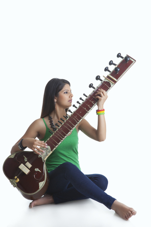 only young women: Young woman playing the sitar Stock Photo