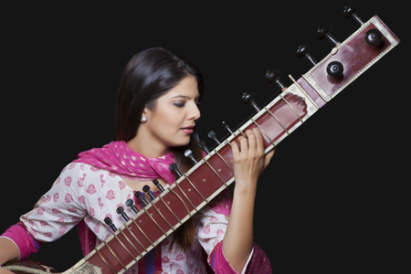 Young woman playing the sitar Stock Photo
