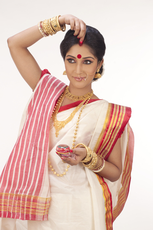 Bengali woman putting sindoor on her forehead Stock Photo