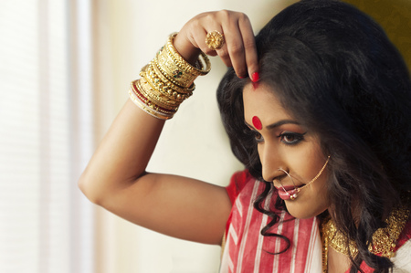 Bengali woman putting sindoor on her forehead Stock Photo