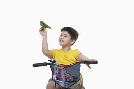 Boy playing with paper airplane while sitting on bicycle against white background
