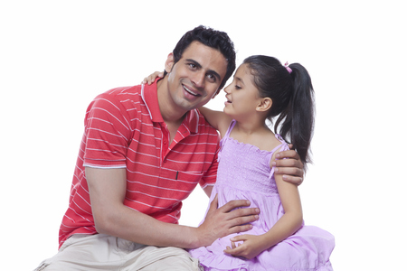 Daughter whispering in fathers ear against white background Stock Photo