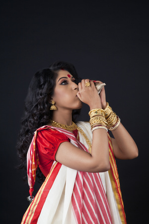 Bengali woman blowing on a conch shell Stock Photo