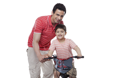 Portrait of father teaching son to ride bicycle against white background Stock Photo