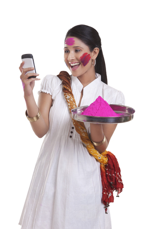 robo: WOMEN with holi colour reading an sms on mobile phone