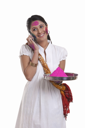 robo: WOMEN with holi colour talking on a mobile phone