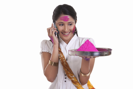WOMEN with holi colour talking on a mobile phone
