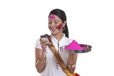 robo: MUJERES con color holi leyendo un sms en el teléfono móvil Foto de archivo