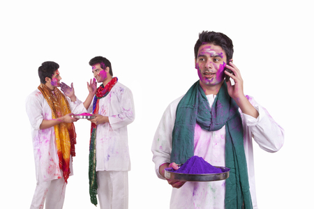 kurta: Young man with holi colour talking on a mobile phone