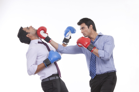 Two male executives boxing