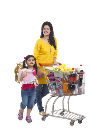 Portrait of mother and daughter with shopping cart