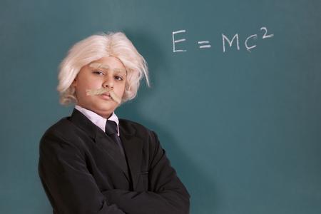 Portrait of boy dressed as Einstein with maths equation