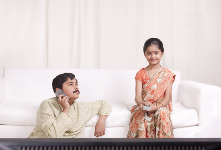 sutra: Boy talking on mobile phone while girl watches tv