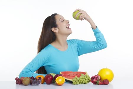 boca cerrada: Mujer a punto de comer una manzana