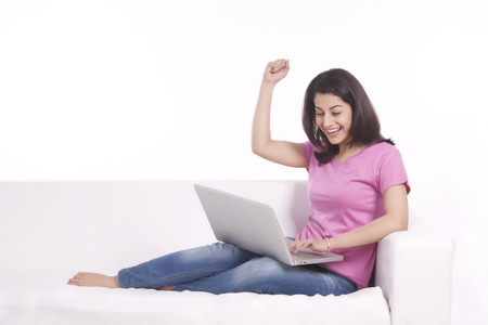 Woman rejoicing while working on laptop Stock Photo