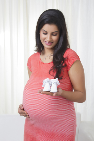 Pregnant mother holding baby shoes