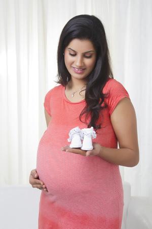 Zwangere moeder met baby schoenen Stockfoto