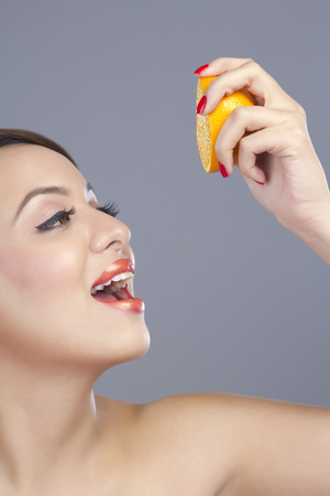 squeezing: Woman squeezing an orange