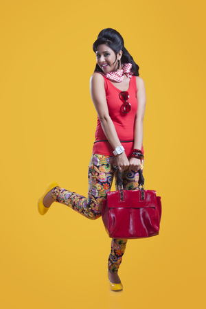 Portrait of retro woman with hand bag smiling