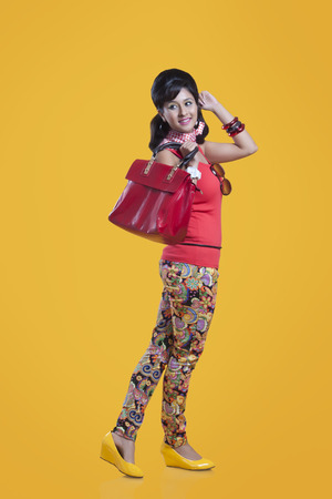 Retro woman with hand bag smiling Stock Photo