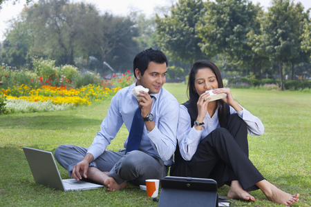 cross legged: Businessman and businesswoman working in a park