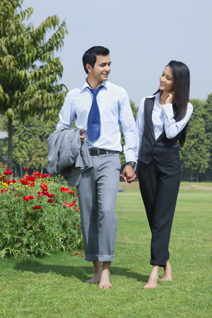Businessman and businesswoman walking in a park Stock Photo