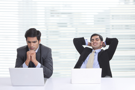 welldressed: Worried businessman using laptop with colleague relaxing at desk in office