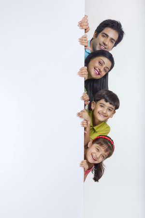 Portrait of family peeking behind white board Stock Photo - 80634563