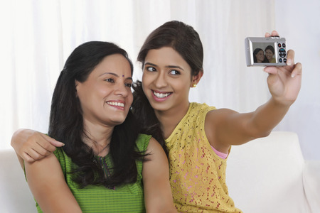 looking away from camera: Mother and daughter taking a self portrait