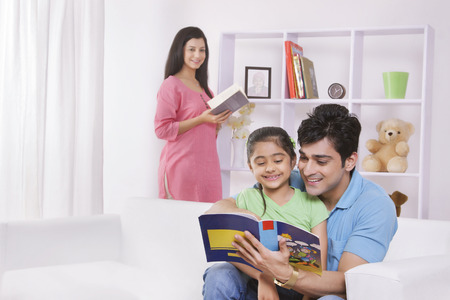green couch: Father and daughter reading a storybook