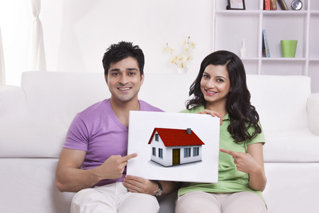 furniture: Portrait of couple pointing to picture of house