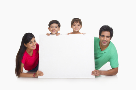 Portrait of family behind white board Imagens
