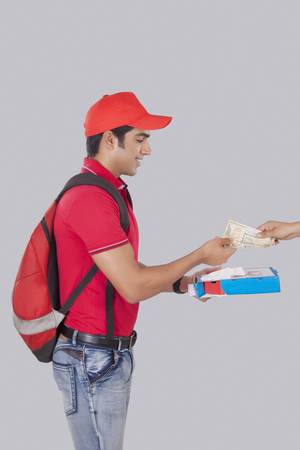 Profile shot of delivery man delivering pizza to customer over gray background