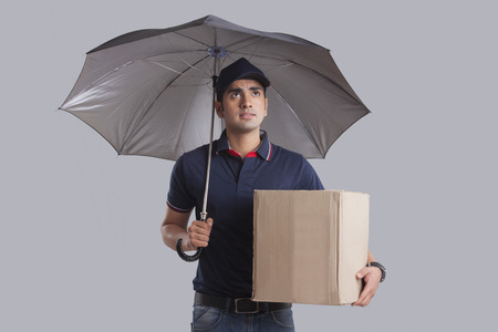Worried delivery man with package and umbrella over gray background