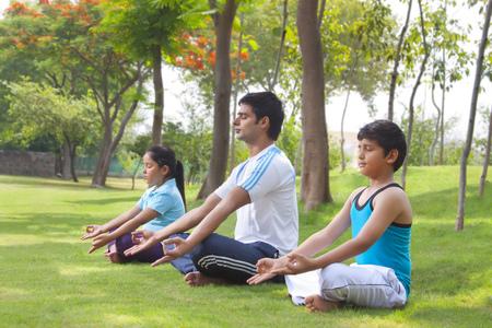 Family meditating outdoors Stock Photo