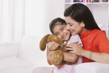 furniture: Mother and daughter playing with stuffed toy Stock Photo