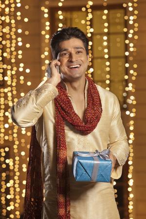 kurta: Man with gift talking on mobile phone Stock Photo