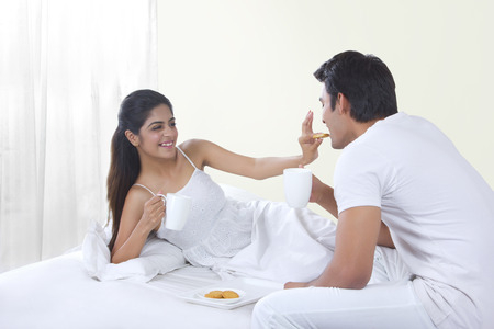Happy young woman feeding biscuit to man in bed