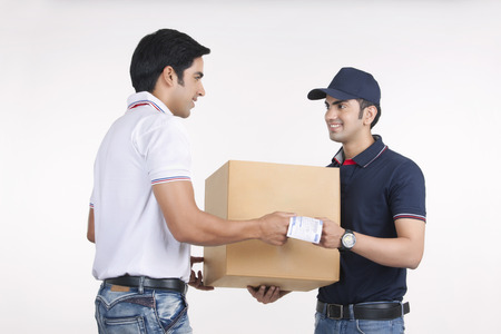 Delivery man giving package to customer against white background