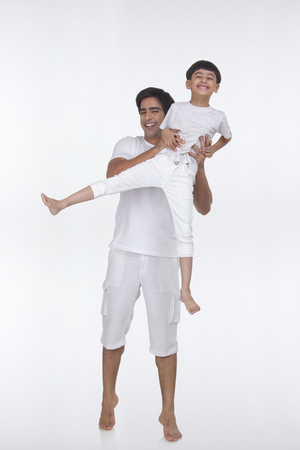 front view: Portrait of father lifting son in the air Stock Photo
