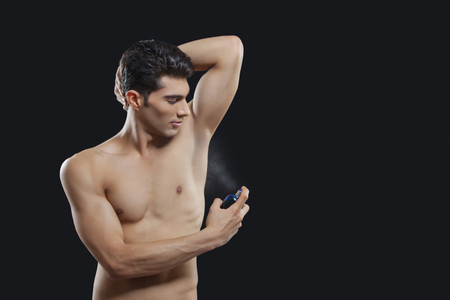 underarms: Young man spraying perfume on underarms