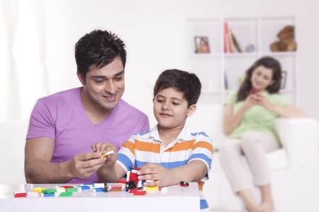 front view: Father helping son with toys