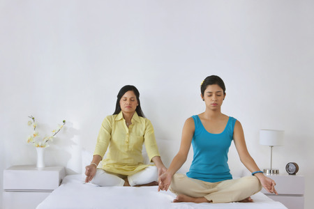 cross legged: Mother and daughter meditating together