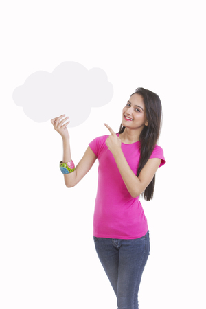 Portrait of happy young woman pointing at thought bubble over white background Stock Photo